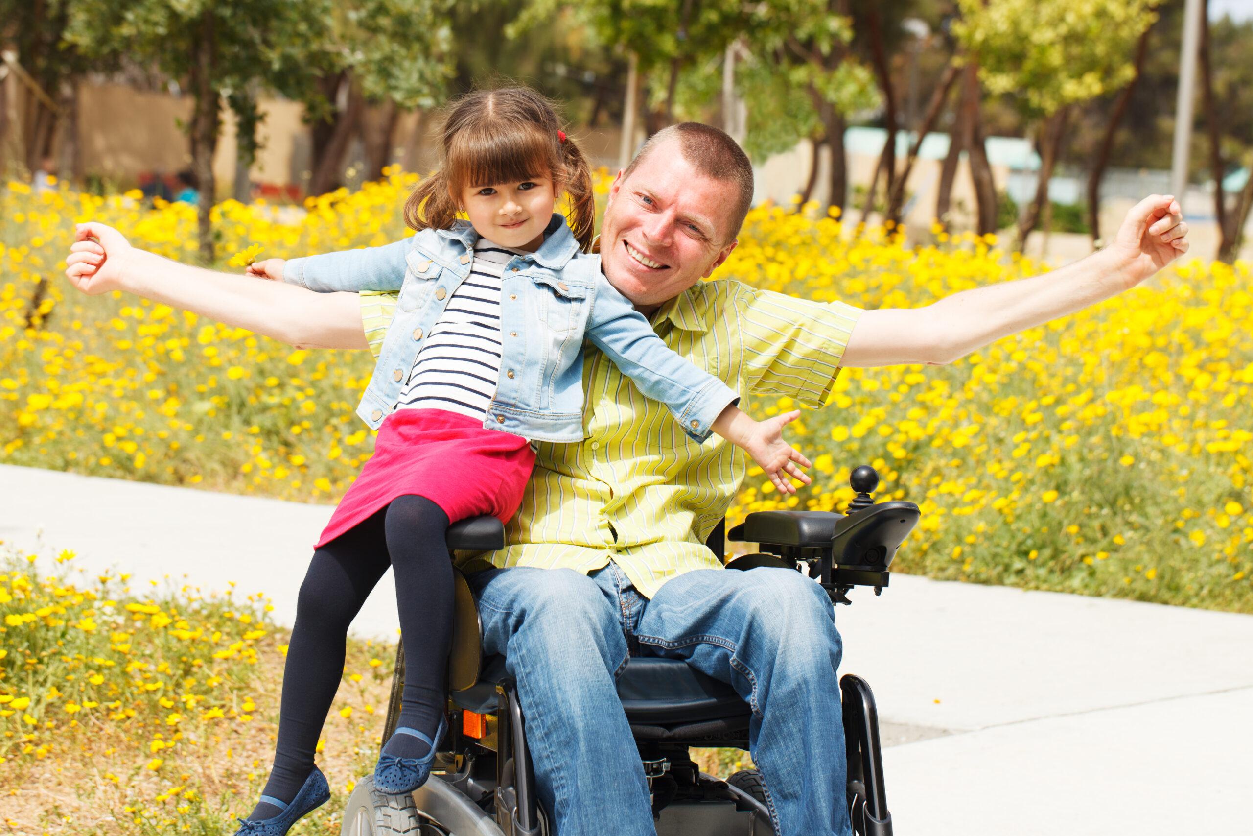 Far og datter ser mot kamera. Far sitter i rullestol. Foto