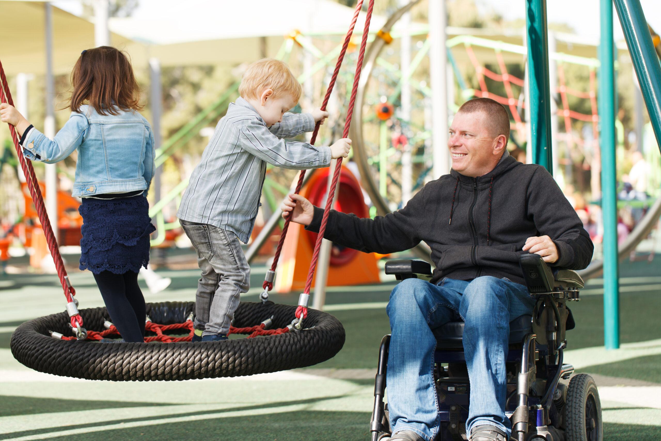 En mann i rullestol som gir to småbarn fart i ei huske. Foto